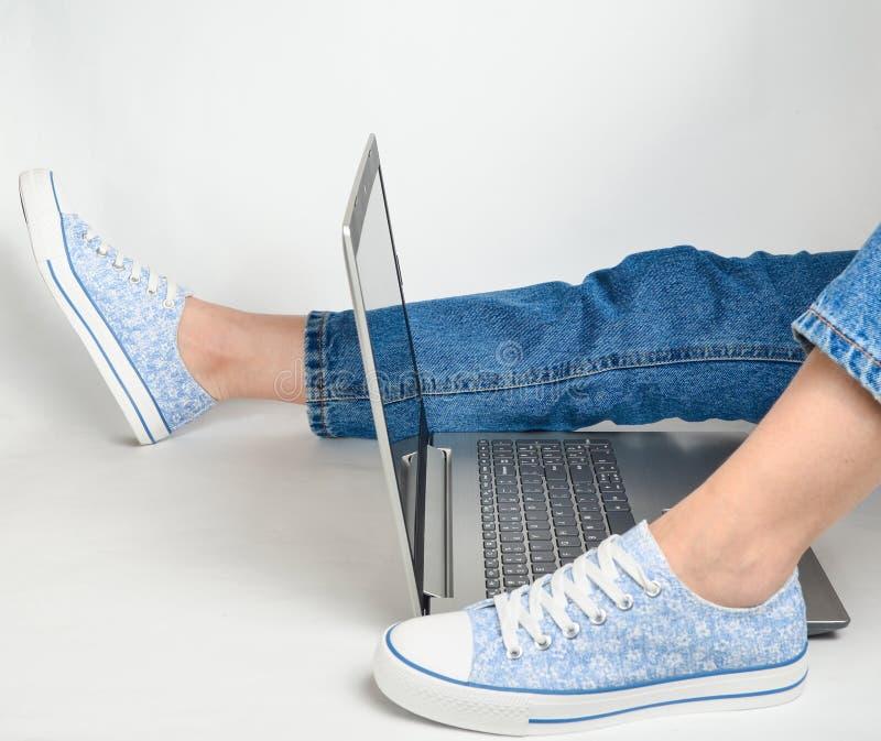 Kvinnliga ben i jeans, gymnastikskor och en bärbar dator på en vit bakgrund Freelancerarbetsutrymme Vila på arbete, brist av idée royaltyfri fotografi