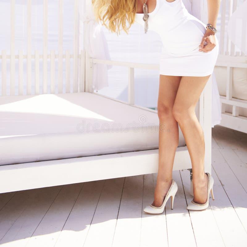 Kvinnliga ben i klassiska skor för vitt mode på en häl royaltyfria foton