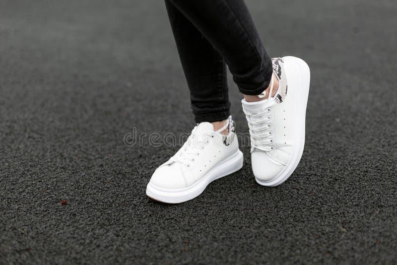 Kvinnliga ben i stilfull svart jeans i gymnastikskor för vitt läder med ormmodellen på asfalten i staden Unga kvinnor på går fotografering för bildbyråer