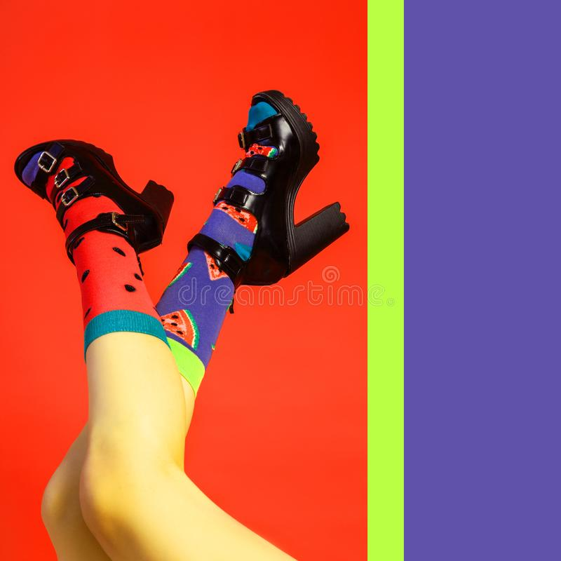 Kvinnliga ben i svarta skor med häl och ljusa färgsockor royaltyfri bild