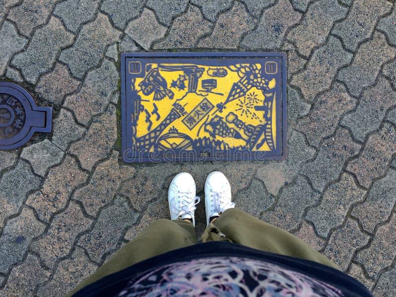 Kvinnliga ben som framme står av en gul kulör manhål av Kobe City, Japan arkivfoton