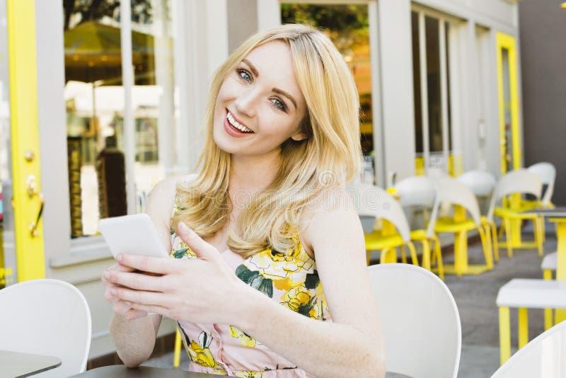 Kvinnliga blonda Caucasian leenden, medan smsa på hennes telefon royaltyfria bilder