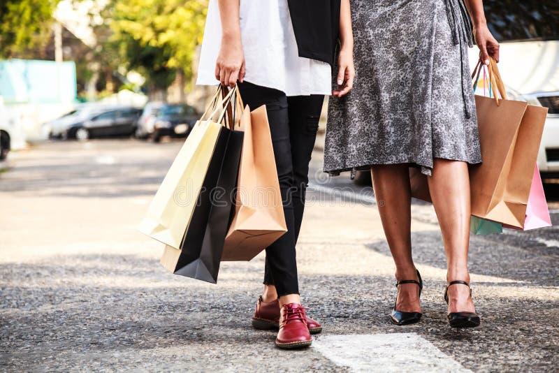 Kvinnliga damer som bär färgrika shoppingpåsar i parkeringsplatsen arkivbild