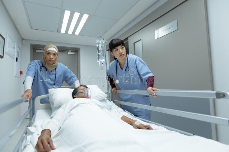 Kvinnliga doktorer som skjuter nöd- bårsäng i korridor arkivfoton