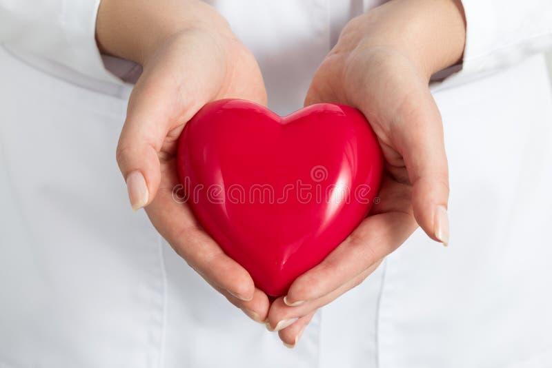 Kvinnliga doktorers händer som rymmer och täcker röd hjärta royaltyfria bilder