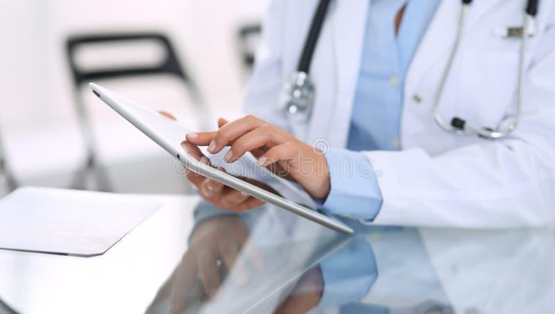 Kvinnliga doktorshänder genom att använda den digitala minnestavlan, medan sitta på exponeringsglasskrivbordet på sjukhuskontoret royaltyfri fotografi