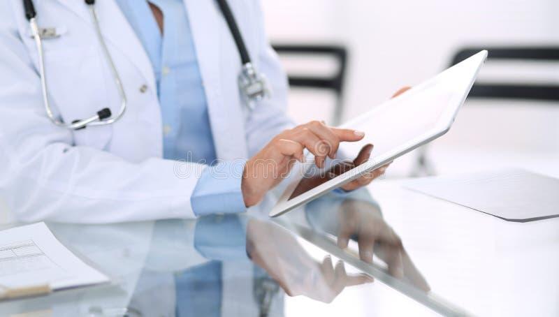 Kvinnliga doktorshänder genom att använda den digitala minnestavlan, medan sitta på exponeringsglasskrivbordet på sjukhuskontoret royaltyfria foton