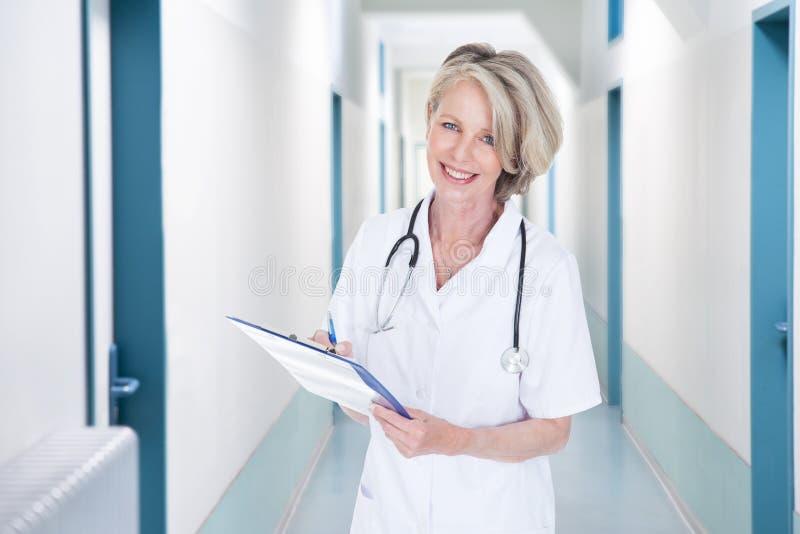 Kvinnliga doktorshandstilanmärkningar i sjukhuskorridor arkivfoto