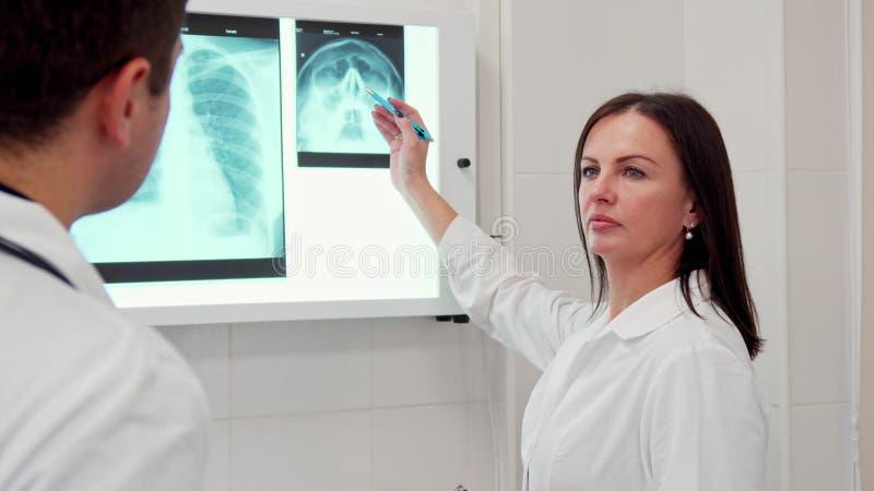 Kvinnliga doktorspunkter ritar på röntgenstrålen av det mänskliga huvudet arkivfoton