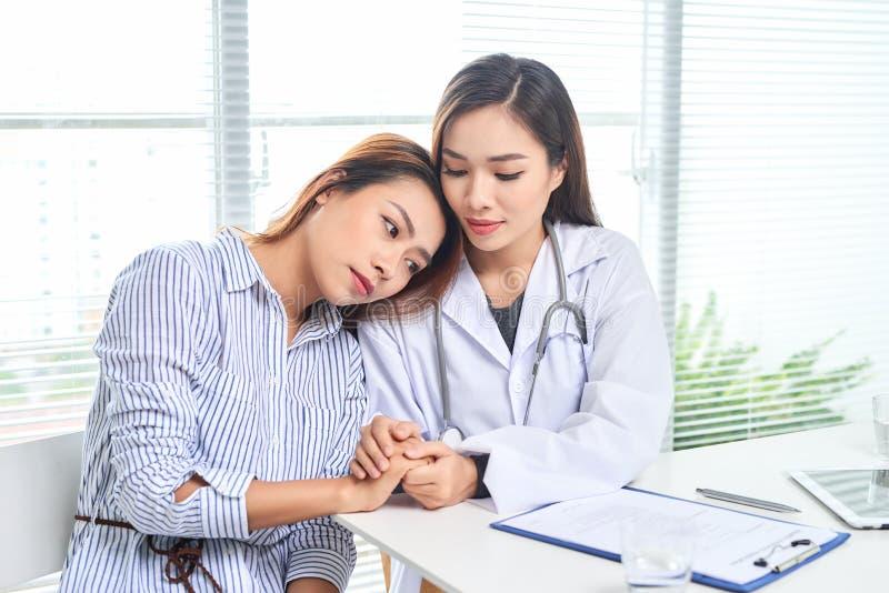 Kvinnliga doktorssamtal till den kvinnliga patienten i sjukhuskontor, medan skriva p? det v?rd- rekordet f?r patienter p? tabelle royaltyfri foto