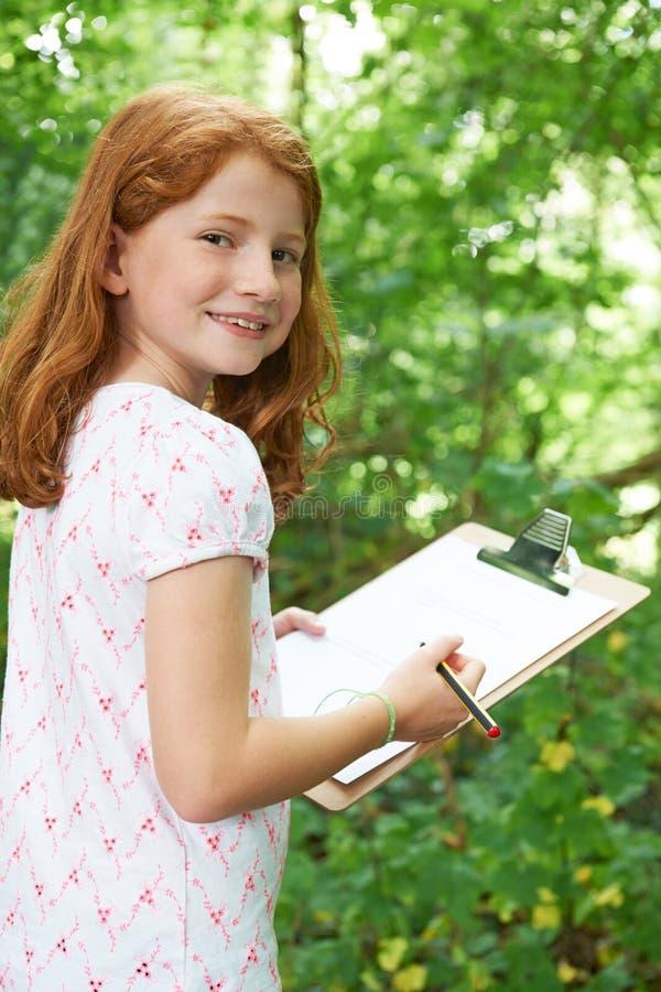 Kvinnliga elevdanandeanmärkningar på tur för skolanaturfält royaltyfria bilder