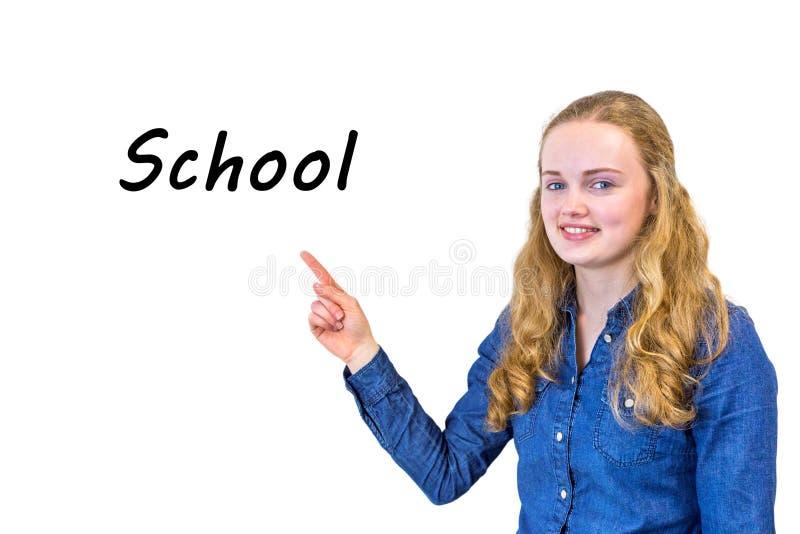 Kvinnliga elevpunkter som uttrycker skola på whiteboard royaltyfri fotografi