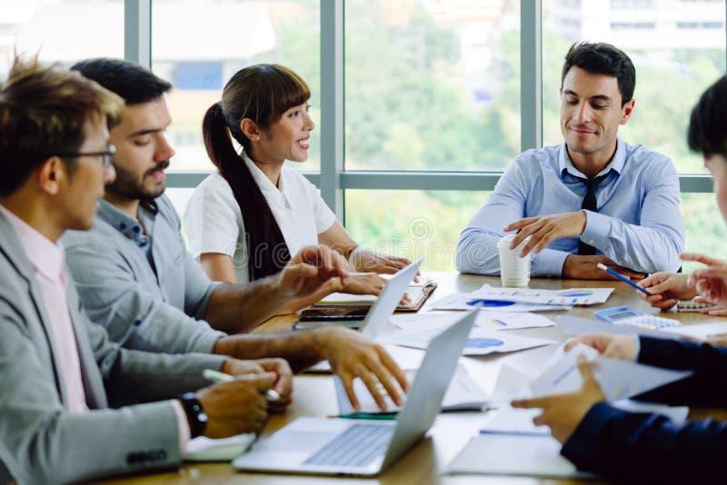 Kvinnliga företagsanställda och män som möter i mötesrummet som talar med en le framsida royaltyfri bild