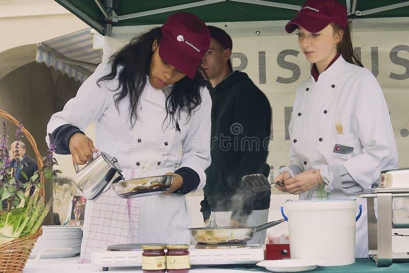Kvinnliga forskare av turismskolan som lagar mat en pannkaka royaltyfria foton
