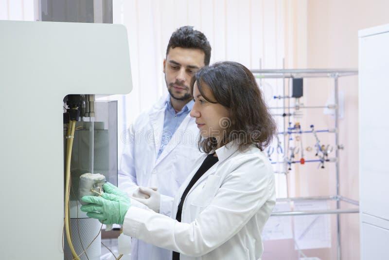 Kvinnliga forskningforskareUses Micropipette Filling provrör i ett stort modernt laboratorium royaltyfria foton