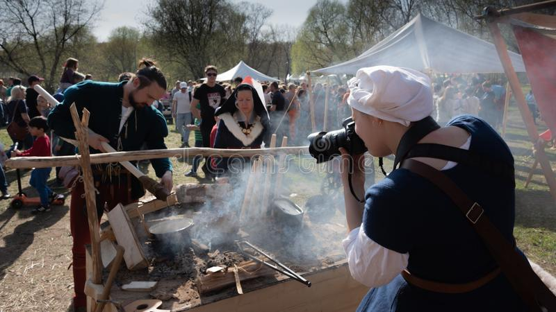 Kvinnliga fotografer i medeltida kläder som tar bilder av den internationella riddaren på ridfesten arkivbild