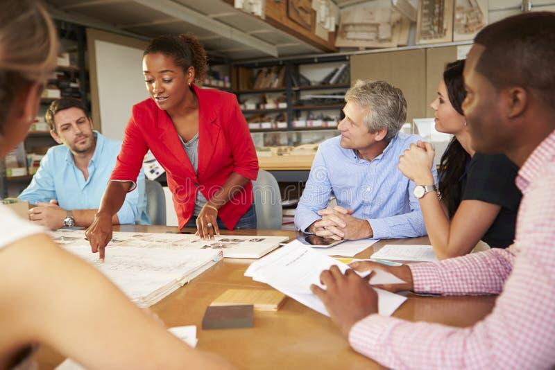 Kvinnliga framstickandeLeading Meeting Of arkitekter som sitter på tabellen arkivbilder