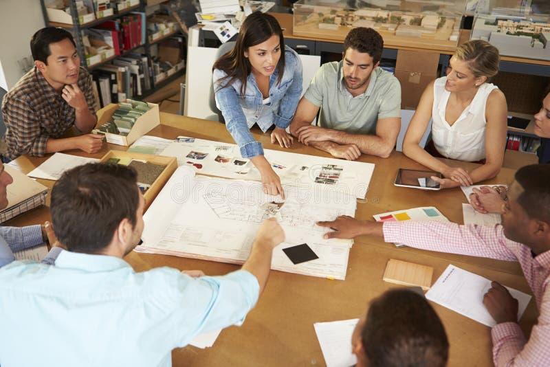 Kvinnliga framstickandeLeading Meeting Of arkitekter som sitter på tabellen arkivfoton