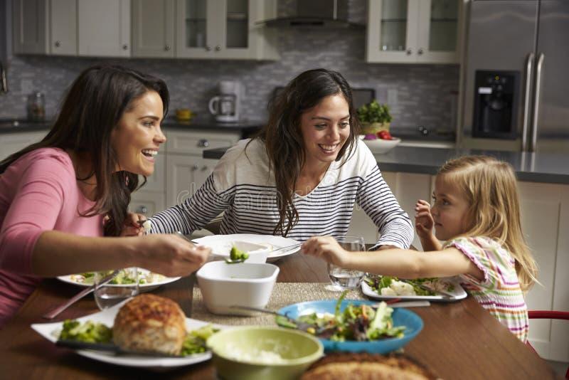 Kvinnliga glade par och dotter som har matställen i deras kök arkivfoto