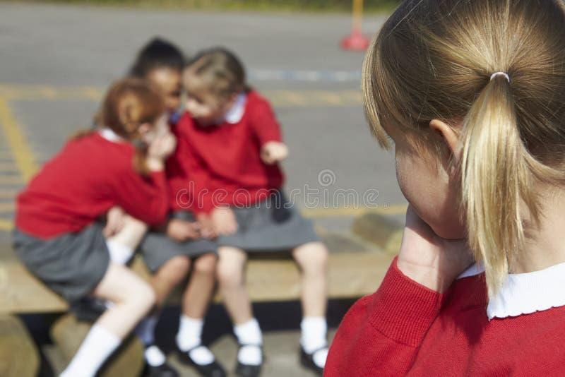 Kvinnliga grundskolaelever som viskar i lekplats royaltyfri bild