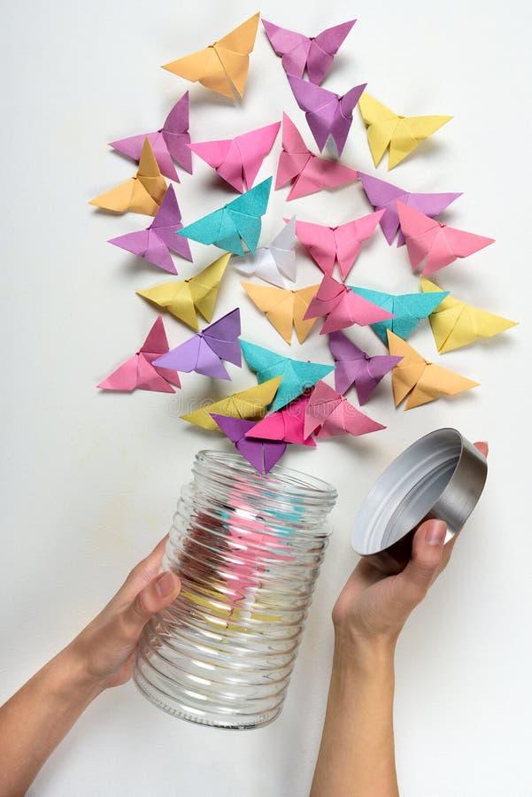 Kvinnliga händer öppnar kruset med pappers- fjärilar på vit bakgrund origami fotografering för bildbyråer