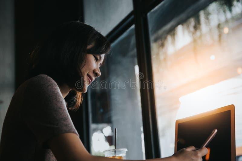 Kvinnliga händer för ung affär genom att använda den smarta telefonen, medan arbeta på datoren arkivfoton