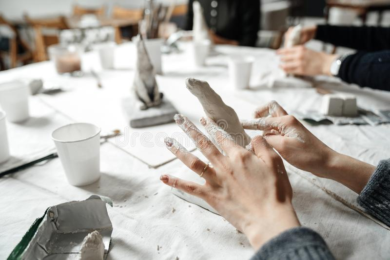 Kvinnliga händer formar elegantly en liten murbrukskulptur på en mästarklass royaltyfri bild