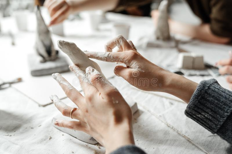 Kvinnliga händer formar elegantly en liten skulptur av murbruk fotografering för bildbyråer
