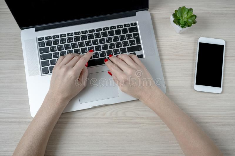 Kvinnliga händer genom att använda bärbara datorn med den tomma svarta skärmen på träskrivbordet royaltyfri foto
