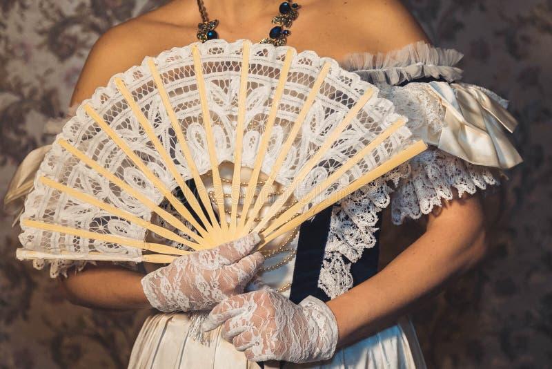 Kvinnliga händer håller en spets- fan i openwork handskar royaltyfri bild