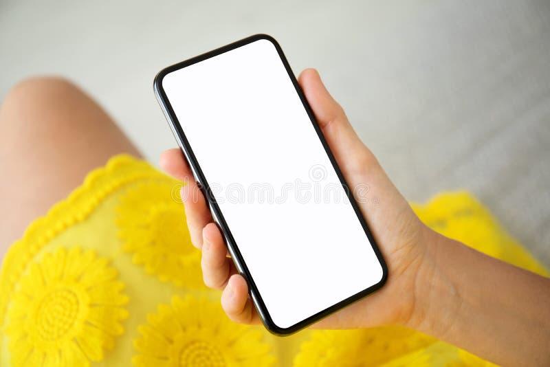 Kvinnliga händer i gul klänninginnehavtelefon med den isolerade skärmen royaltyfri foto