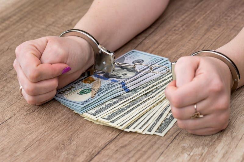 Kvinnliga händer i handbojor på dollar arkivfoto