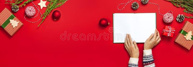 Kvinnliga händer i stucken tröja rymmer den öppna rena anteckningsboken, gåvaaskar, granfilialer på röd bakgrundslägenhet lägger  arkivbilder