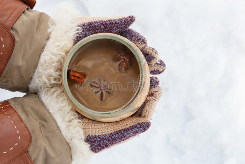 Kvinnliga händer i stucken vit kopp för grå tumvantehåll av kryddig cof arkivbild