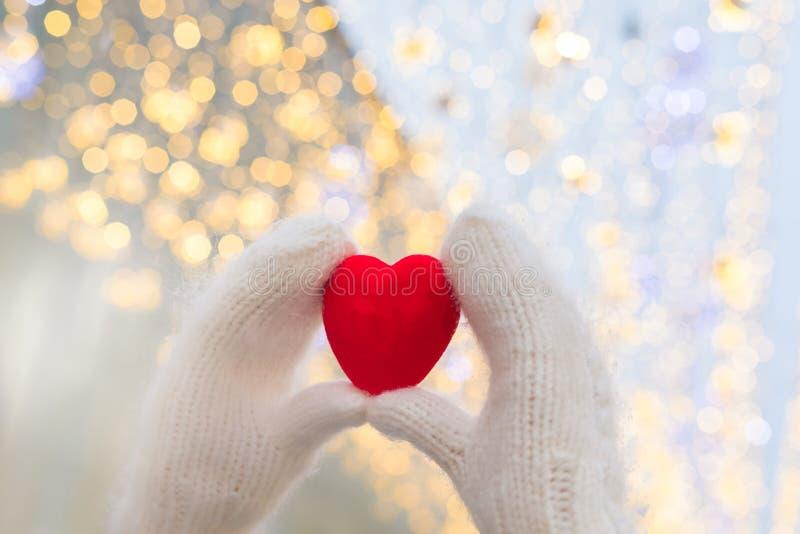 Kvinnliga händer i vita stack tumvanten med röd hjärta på att blänka feriebakgrund Begrepp för St Valentine Day arkivfoton