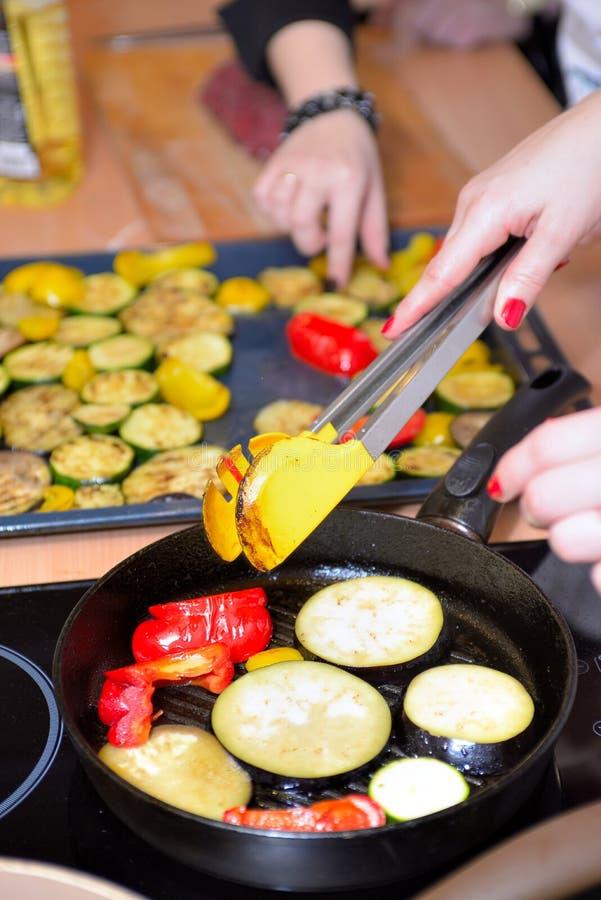 Kvinnliga händer kastar veggies in i en panna arkivfoton