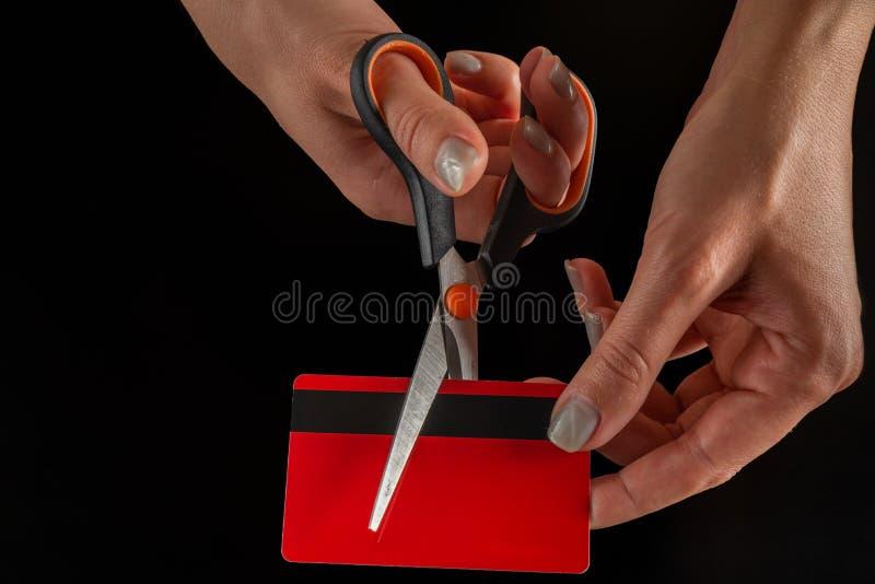 Kvinnliga händer klipper med det röda debitering-/krediterings-/shoppingkortet för sax med den svarta linjen på den svarta bakgru arkivbilder