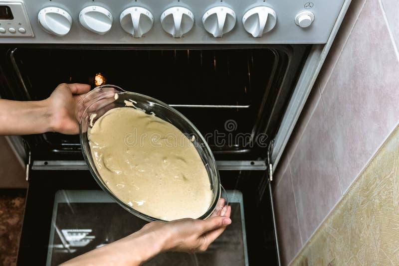 Kvinnliga händer lägger en glasbakskål med deg i ugnen Processen att göra en snygg, snygg, homemad kaka arkivbild