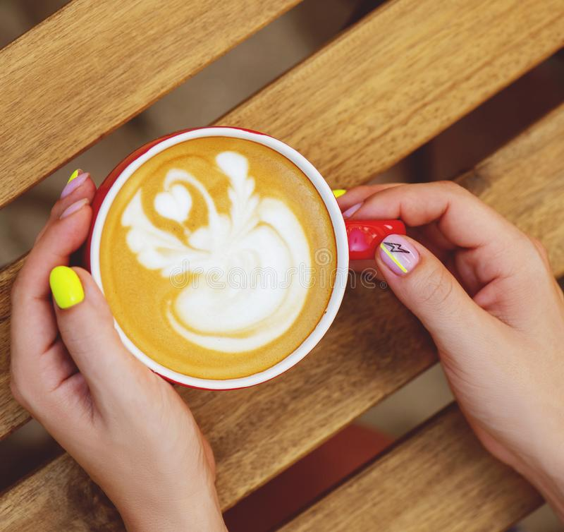Kvinnliga händer med den moderiktiga koppen kaffe för neonmanikyrinnehav arkivbild