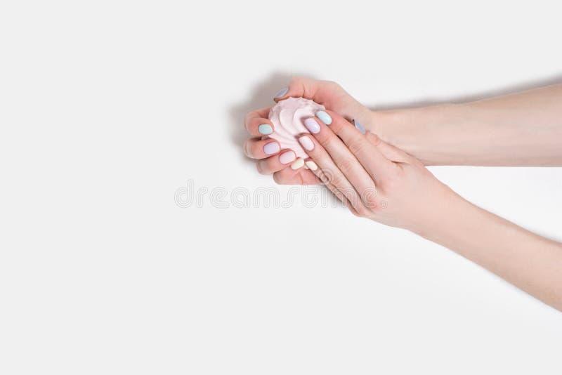 Kvinnliga händer med en försiktig manikyr på en vit träbakgrund Marshmallow i händerna arkivfoton