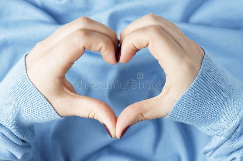 Kvinnliga händer med en manikyr i formen av en hjärta på en blå bakgrund arkivfoto