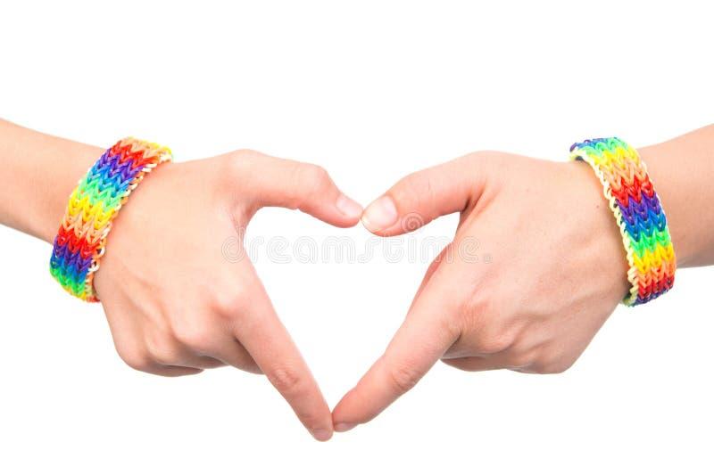 Kvinnliga händer med ett armband som mönstras som regnbågen, sjunker visninghjärtatecknet På white royaltyfri bild