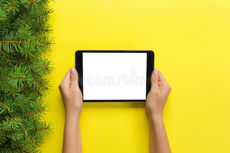 Kvinnliga händer med minnestavladatoren på gul julbakgrund Bästa sikt för Xmas-trädfilial royaltyfria foton