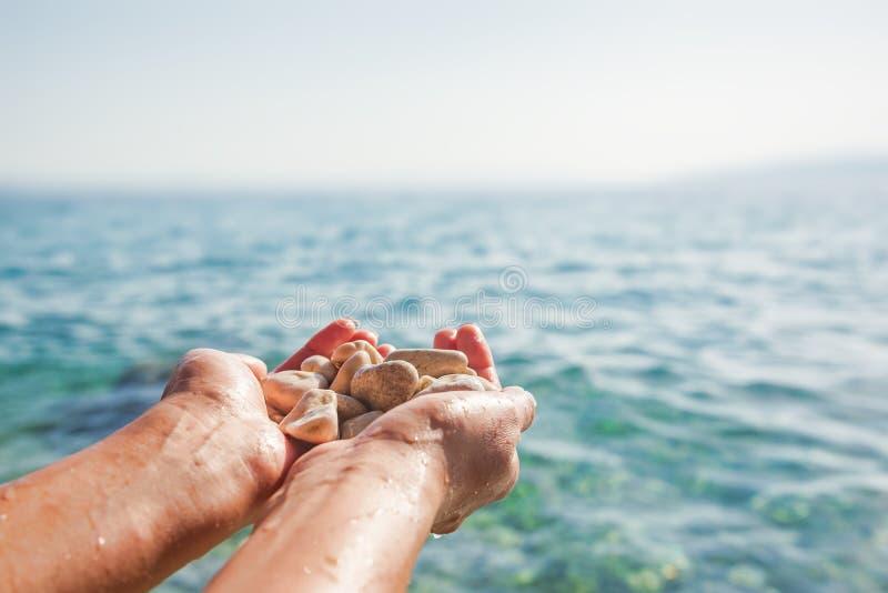 Kvinnliga händer på bakgrunden av havet eller havet rymmer havsstenar royaltyfri foto