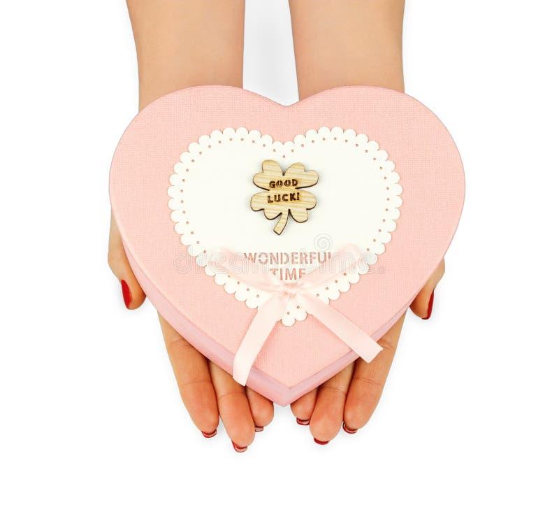 Kvinnliga händer rymmer en gåvaask i form av en hjärta royaltyfri foto