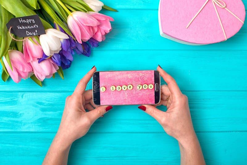 Kvinnliga händer rymmer en telefon med ett meddelande av förälskelse Valentin dagbakgrund med buketten av tulpan och en gåvaask i royaltyfri bild