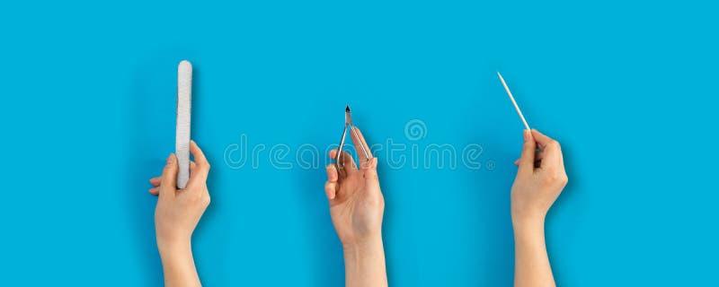 Kvinnliga händer rymmer manikyrhjälpmedel royaltyfri foto