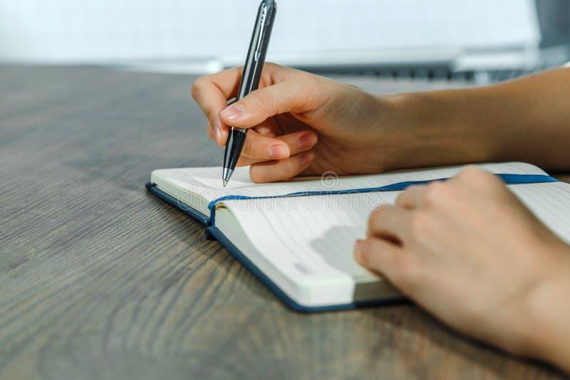 Kvinnliga händer skriver i en anteckningsbok arkivbild
