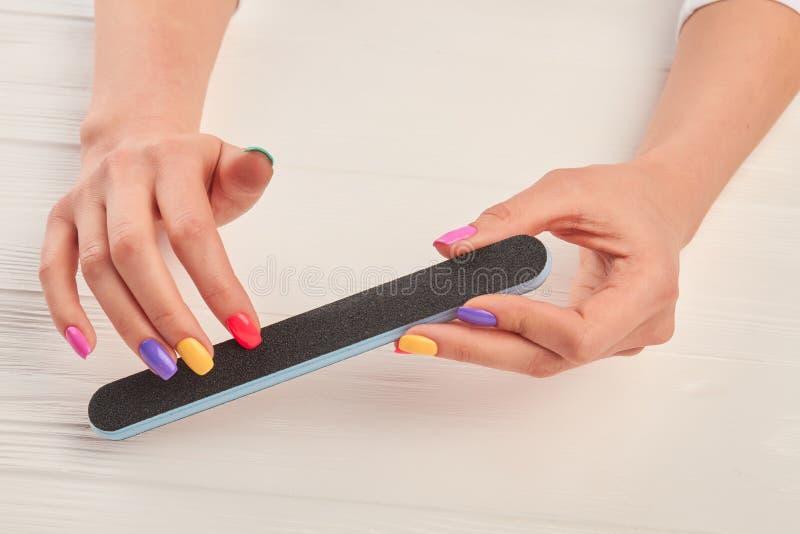 Kvinnliga händer som att spara spikar med, spikar mappen arkivfoton