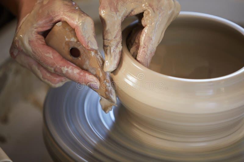 Kvinnliga händer som formar lera arkivbild